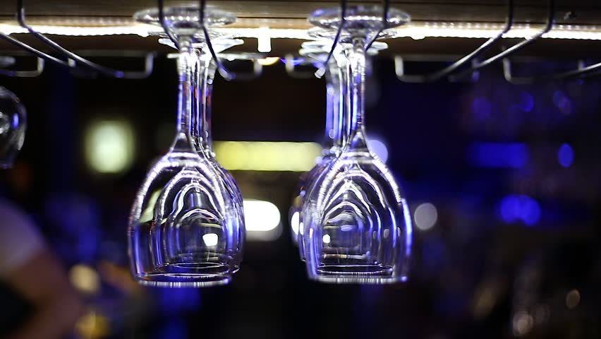 Clean wine glasses hang over the bar in a restaurant or in a nightclub | Shutterstock HD Video #1013991242