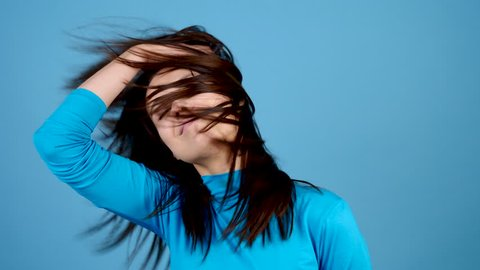 Happy beautiful woman shakes her head on blue background in studio. Positive girl with long dark hair