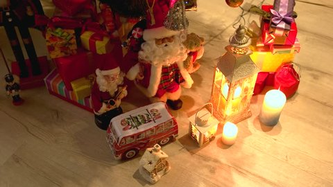 Gift boxes and Christmas decorations. Santa Claus toy, boxes with presents, lantern, gingerbread house and candles on wooden background. Merry Christmas and happy New Year.