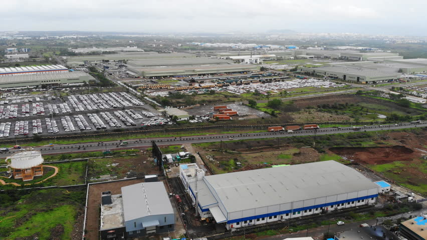 Aerial panoramic view of industrial zone in city of Pune, many new cars parked in rows, modern factories and warehouses - Maharashtra, landscape panorama of India, Asia from above