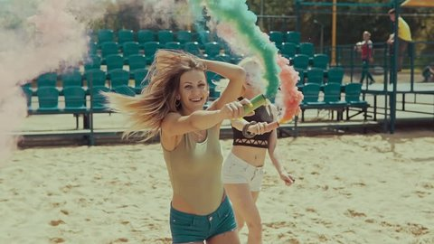 Young hipster girls in shorts runs in sand field with tribune at background waving colored smoke. Young girls have fun and jump outdoors in slow motion. Party concept