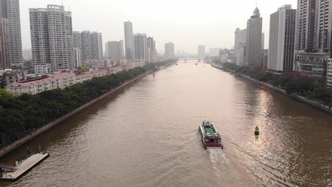 One ferry sail at Pearl River, aerial follow camera, tall buildings on banks, green trees grow along water. Typical light mist in air at evening time. Many tall and low-rise buildings around river