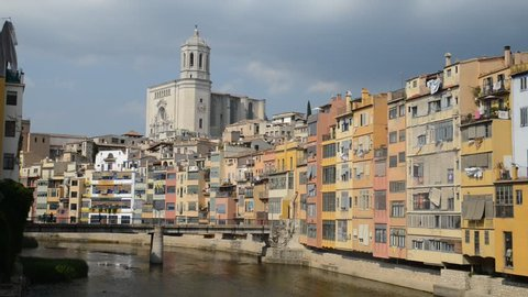 Colorful houses and the cathedral of Girona reflecting in the Onyar River, Spain.