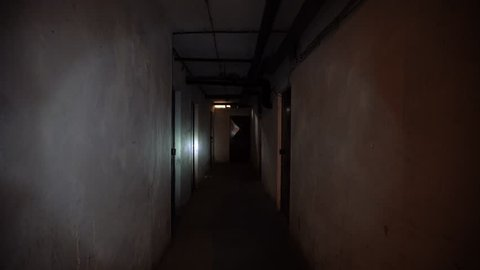 Urban explorer roams throught abandoned corridor or basement and gets scared by a ghost of a girl in white. First person POV shot.