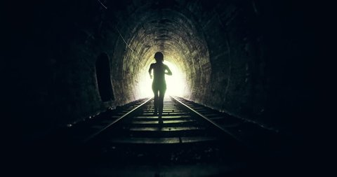 Salvation, hope and freedom concept scene. Person running in dark tunnel toward bright light in the end and escapes from the darkness through open gate