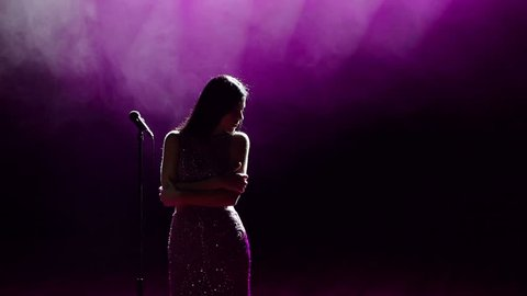 Young beautiful singer sings on stage in the light white and pink spotlights.