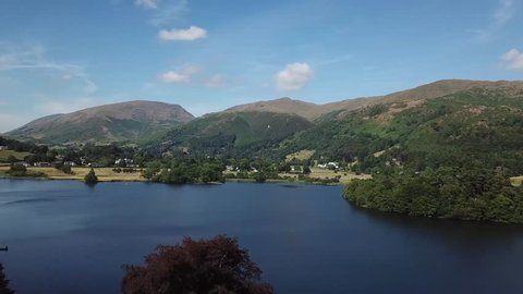 Aerial drone footage flying past trees and over a lake | The Lake District | 4K