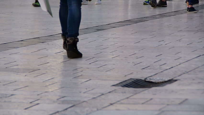 Human legs walking - Tourists at People`s Square  In Split, Croatia