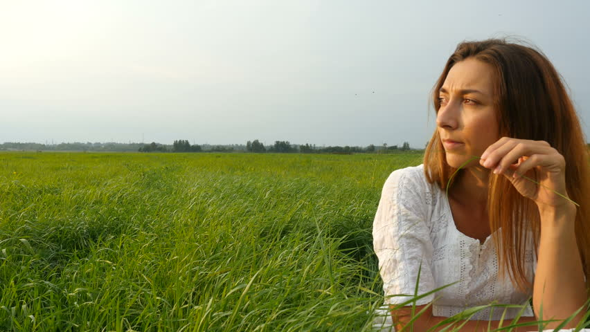 Portrait happy young woman on a summer walk in field. Cute girl sitting on the green grass and dreaming. Beautiful young woman enjoying nature in summer evening. Grassy summerfield   | Shutterstock HD Video #1014099782