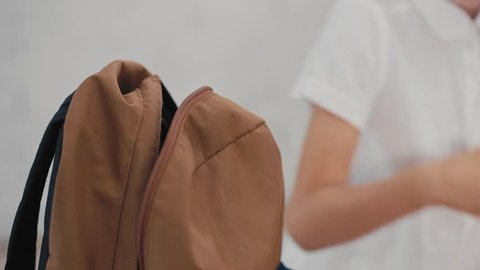 Schoolboy puts a tablet computer in a backpack. Back to School.