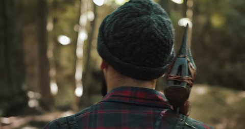Walking bearded lumberjack with axe. Man in a cap walks through the woods in search of the tree. View behind the back