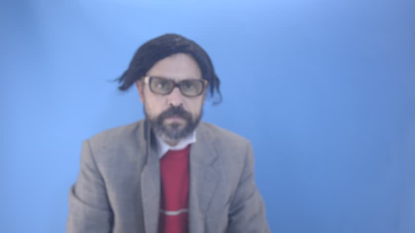 An untidy bizarre man, wearing big patched glasses and a toupee, approaching and looking through a loupe (magnifying glass) to the camera and examining it up close, over a light blue background.