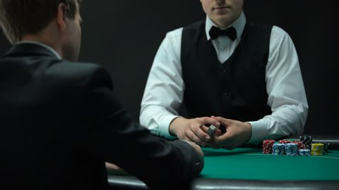Experienced croupier making shuffling tricks and dealing cards, chance to win