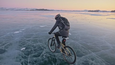 Man is riding a bicycle on ice. The cyclist is dressed in a gray down jacket, backpack and helmet. Ice of the frozen Lake Baikal. The tires on the bicycle are covered with special spikes. The traveler