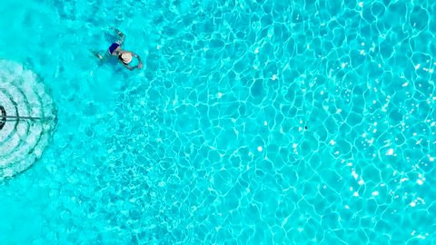 View from the top as a woman in a blue swimsuit swims in the pool