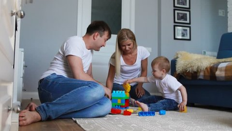 Happy family dad mom and baby 2 years playing lego in their bright living room. Slow-motion shooting happy family