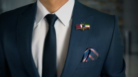 Businessman Walking Towards Camera With Friend Country Flags Pin Qatar - Equatorial Guinea