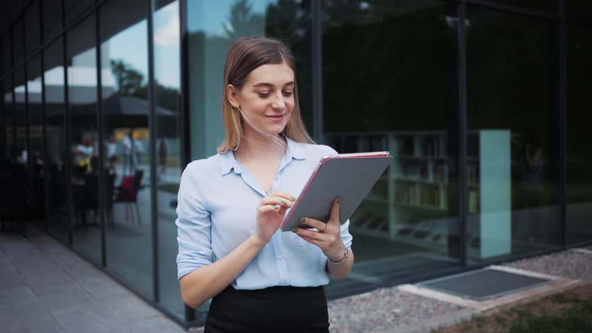 Smiling beautiful business lady uses tablet computer stand near business center attractive technology girl internet young digital work screen smart one student touch professional holding looking   Shutterstock HD Video #1014212822
