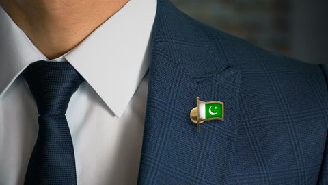 Businessman Walking Towards Camera With Country Flag Pin - Pakistan