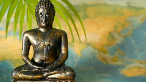 World Map. Journey Explore Concept. Abstract travel destination background with copy space. Trip Southeast Asia. Sitting buddha as symbol of asian culture. Close up slill life, soft selective focus.