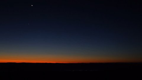 Morning dark sunrise with blue sky and flickering city lights in Dolly Sods, Bear Rocks, West Virginia with overlook of mountain valley, stars, moon, and Jupiter, Venus, Mars planets