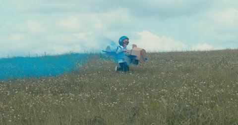TRACKING Cute little dreamer kid boy wearing blue helmet and aviator glasses flying in a cardboard airplane with attached smoke bombs through the field, pretending to be a pilot. 4K UHD 60 FPS SLO MO