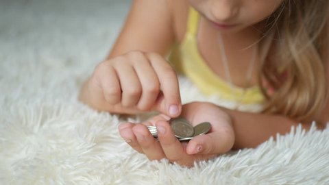Young girl counting coins, kid saving money. Child Counting His Savings. Little child counting money.