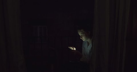 Young blonde Woman Swiping Smart Phone Internet social media Device behind Curtains at Night. A Smiling Student Girl in Evening Light Communicating with Technology, a Bohemian Millenial at Twilight.