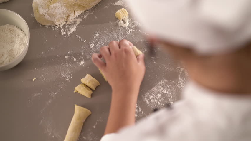 4K cooking footage, close up female cook preparing gnocchis out of fresh dough in kitchen, over shoulder view