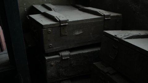Old wooden and dusty boxes in a storage. Clip. Dusty furniture inside ancient house. Old wooden boxes in abandoned house