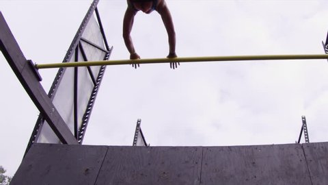Slow motion woman making leap in obstacle course