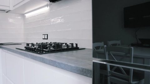 interior of white modern compact kitchen.LED lamps and false ceiling. gas stove, chrome plated faucet.