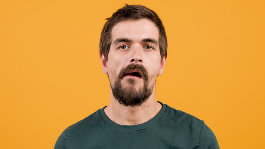 Close up portrait of bored man chewing gum on yellow orange background | Shutterstock HD Video #1014304952