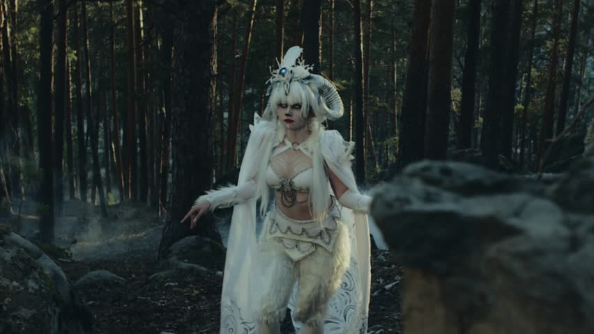 Fantasy creature satyr is walking in a woodland. Woman dressed in a costume with horns and white walleyes, scary artistic filming