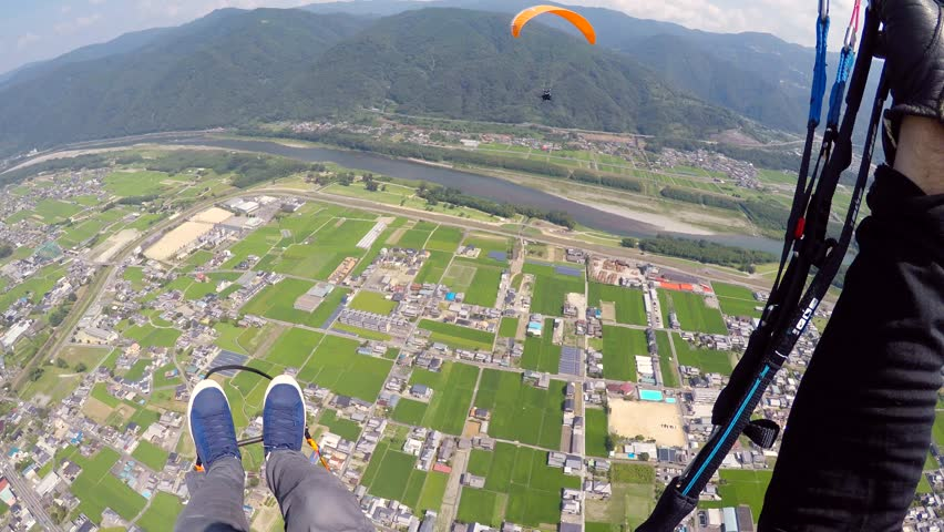 Solo paraglider wave while passing a tandem paraglider in Japan in Summer