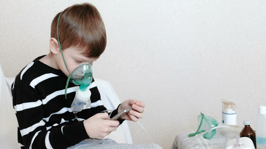 Use nebulizer and inhaler for the treatment. Boy inhaling through inhaler mask and playing the game in his mobile phone. Side view.