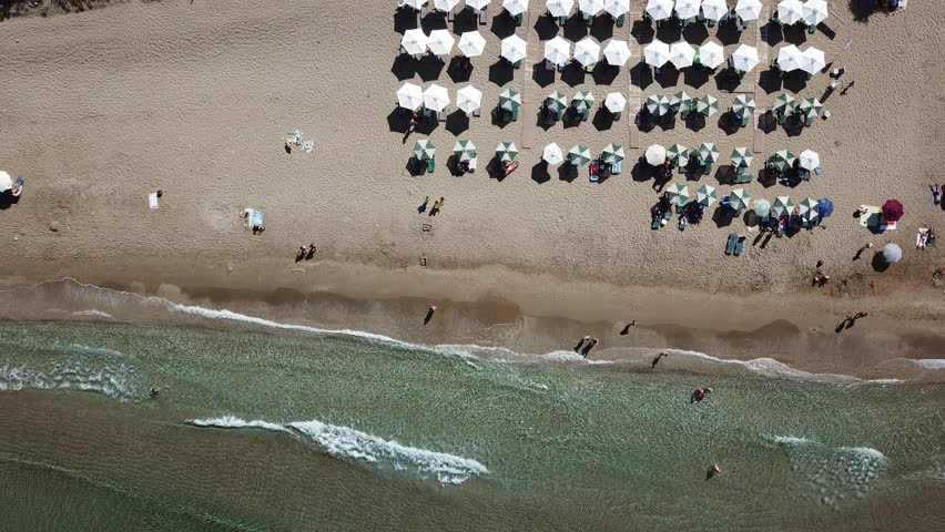 Birds eye view of beach umbrellas as waves lapping against the shore in Corfu Greece on Summer day