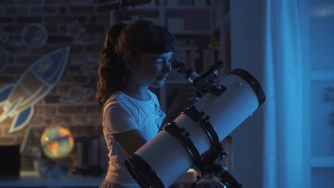 Cute girl watching the stars with a professional telescope at night in her room, imagination and childhood concept