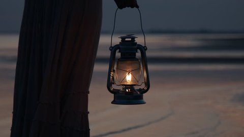 Girl in dress holding old kerosene lantern in her hand on beach after sunset at night