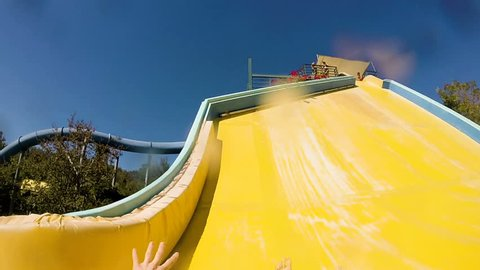 descending down on water slide in water park, first person view