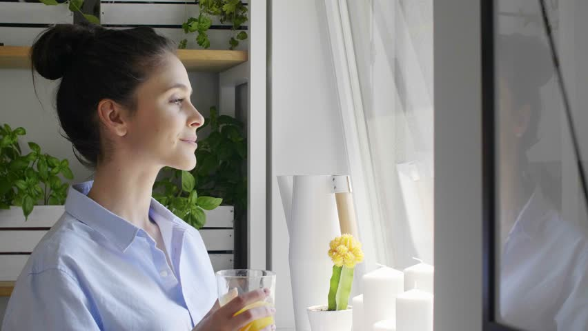 Young woman looking through window and drinking orange juice at home