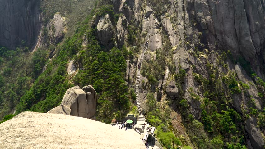 Panning up massive stairs up the side of Chinese Huangshan mountain. Very long staircase up Yellow Mountain in China. Walking up thousands of steps to the top peak for tourists.