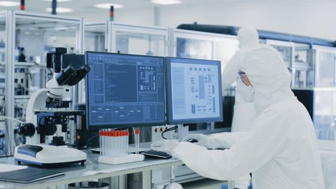 In Laboratory Over the Shoulder View of Scientist in Protective Clothes Doing Research on a Personal Computer. Modern Manufactory Producing Semiconductors.