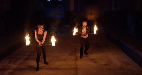 Stunt Man and Woman Performing Fire Show In Darkness Playing With Fire Low Light Fog Slow Motion 8k Red Epic