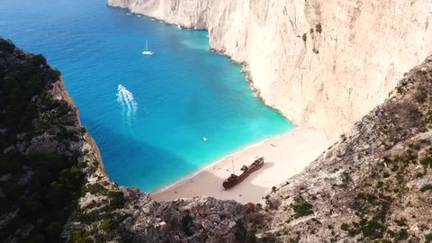 Aerial top view video of iconic Navagio or Shipwreck ship as seen from above in one of the most beautiful beaches in the world with deep turquoise clear sea, Zakynthos island, Ionian, Greece