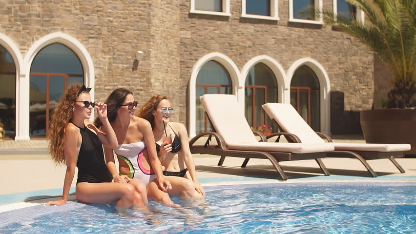 Beauty and body care. Three Seductive women in stylish swimming suite, relaxing in indoor spa swimming pool at hotel. Refreshment after hot sunny day.