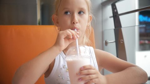 Little girl child in cafe drinking milk cocktail cacao with milk. Child drinks a milkshake sits in a cafe.
