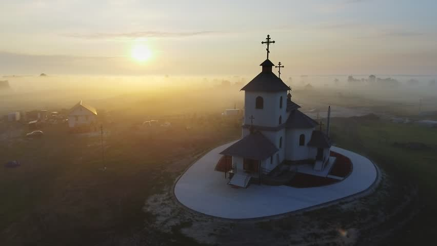 Aerial footage video of small village church at the foggy morning. Sunrise time. Kyiv region, Ukraine. Flying over the Desna river