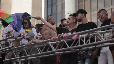 Medellin, Colombia - July 11, 2018: Men waving gay flag on a truck during parade