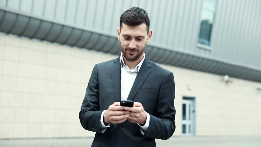 Successful Businessman Standing in the Foreground. Holding Mobile Device in his Hands. Looking on Smartphone's Screen. Young Man Wearing Official Clothes. Classical Jacket. Business Lifestyle. | Shutterstock HD Video #1014544442